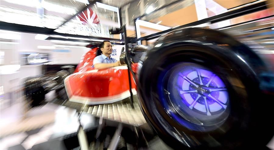 A visitor tries out a driving simulator at Chinese telecom giant Huaweis exhibition during the first World Intelligence Congress in Tianjin