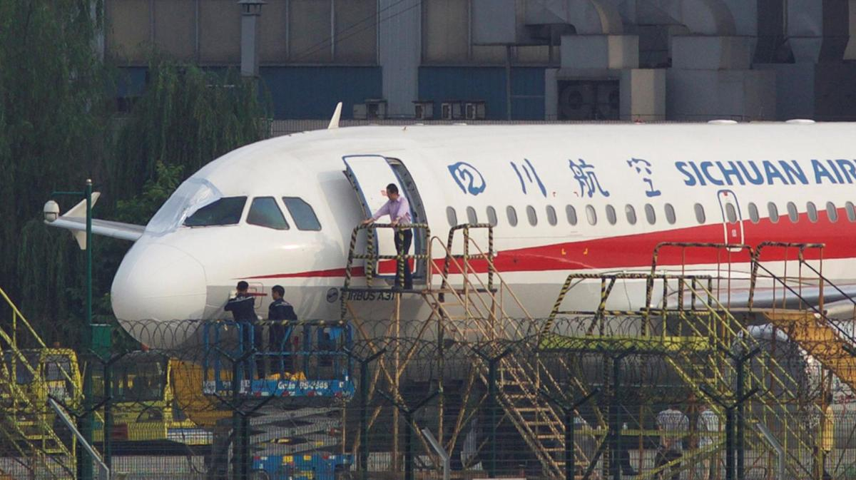 Workers inspect a Sichuan Airlines aircraft that made an emergency landing