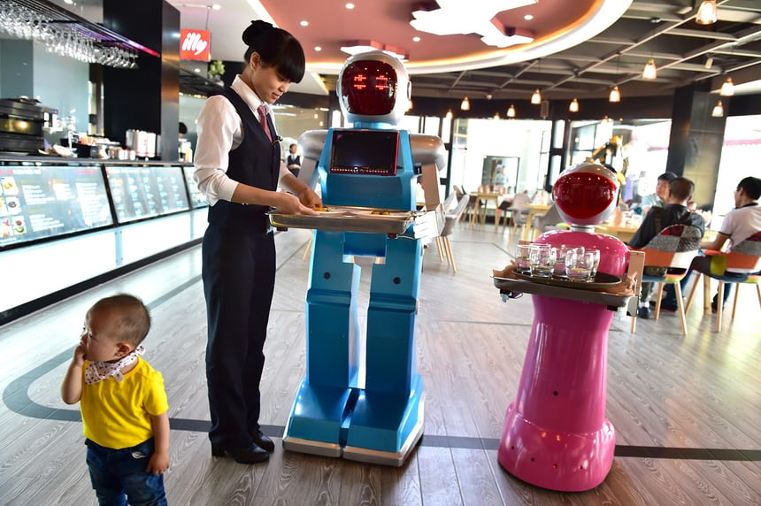 a couple of AI waiters Little Blue and Little Peach at a robot themed restaurant in Yiwu