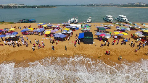 Tourists line the waterfront at the Yudai Beach sceinic area in Boao Hainan Province