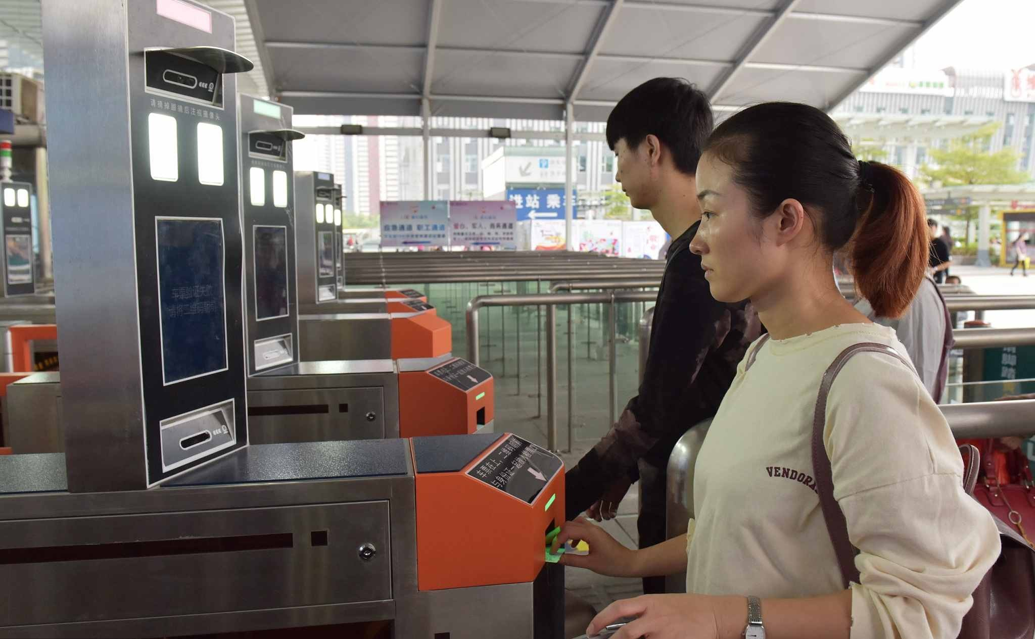 Passengers are identified by facial recognition system by swiping ID cards at Shenzhen North Railway Station