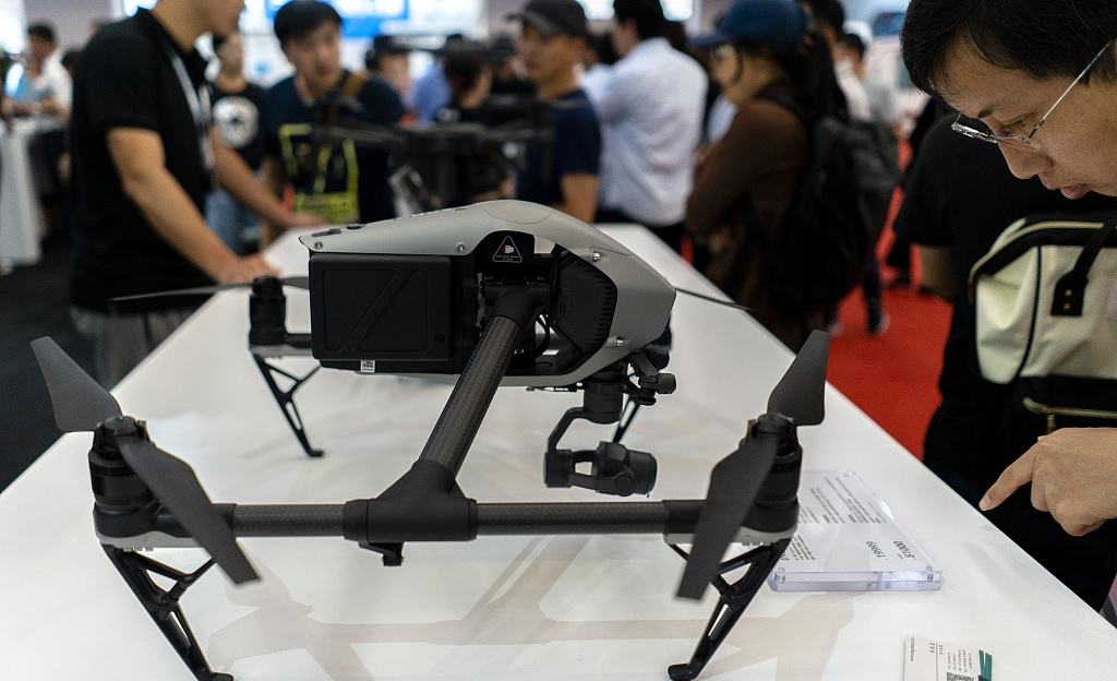 A visitor looks at an unmanned aerial vehicle of DJI on the 2nd World Intelligence Congress held in Tianjin on May 18 2018