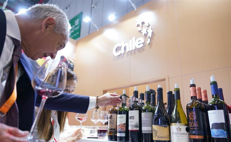 A man looks at wine from Chile at the first China International Import Expo in Shanghai