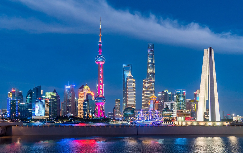 Bright colors glow and reflect on the river in this night view of the Bund in Shanghai
