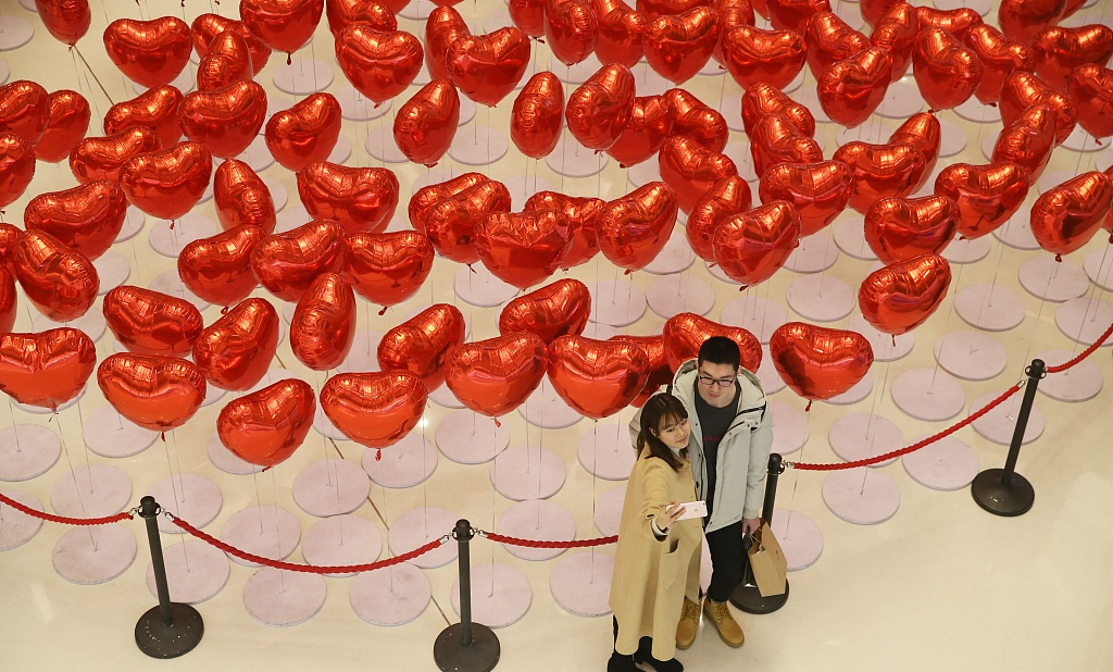 Two lovers take a photo in a shopping mall decorated with heart shaped balloons in Qingdao East Chinas Shandong province