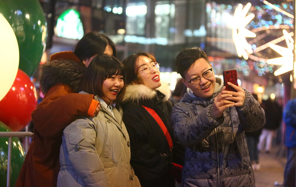 Visitors take selfies while shopping at Sanlitun in Beijing