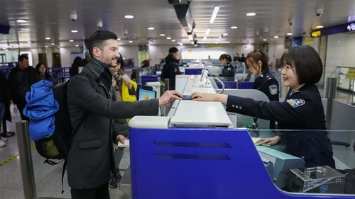 Policewoman Wang Qian R helps a foreigner get cleared at immigration inspection checkpoint of the airport in Qingdao