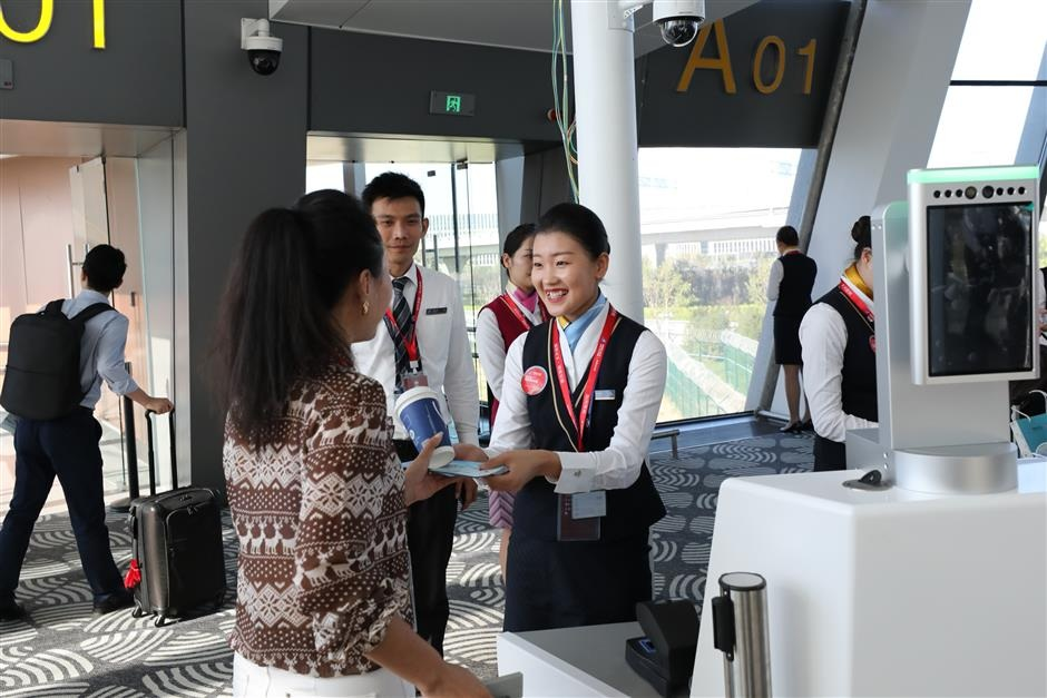 Crew members welcome the passengers at the first commercial flight at the Daxing airport