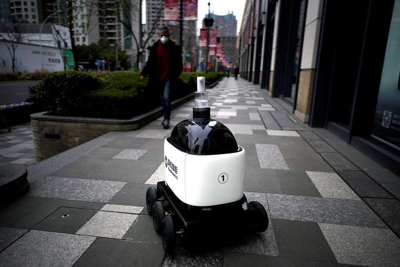 A robot with a dispenser for hand sanitizer goes around a shopping complex as the country is hit by an outbreak of the novel coronavirus in Shanghai