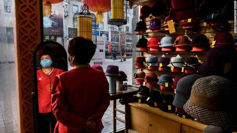 A sales clerk wears a mask as she waits for customers at a hat shop in Beijing