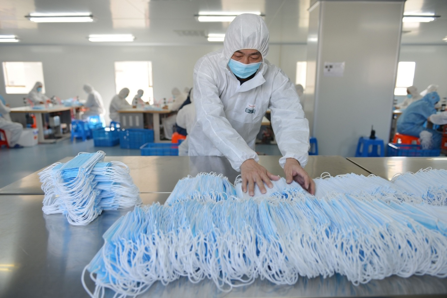 A worker at a factory in Nanjing sorting face masks being produced to satisfy increased demand