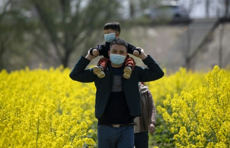 People wearing face masks walk through a rapeseed farm used to produce canola oil in Chinas central Jiangxi province that borders Hubei province