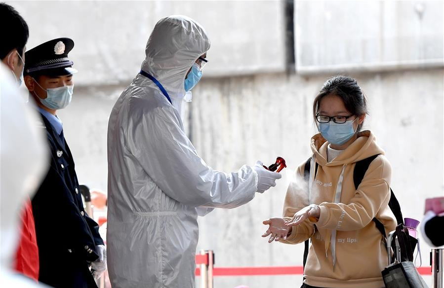 A staff member disinfects a students hands at the No. 9 Middle School in Zhengzhou central Chinas Henan Province