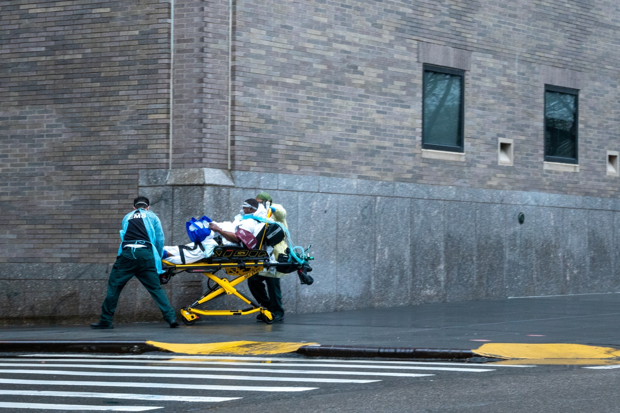 Medical staff transport a patient on the side walk outside of Mount Sinai hospital in New York on April 13