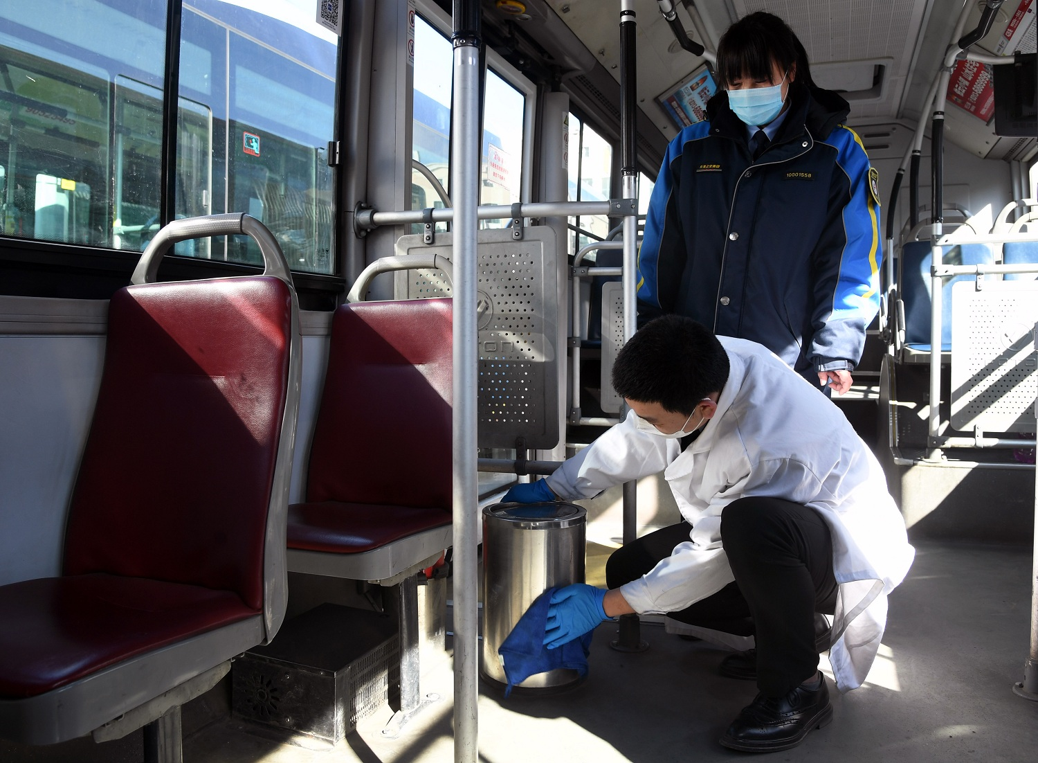 Bus driver Li Tengfei front disinfects the garbage can on the bus