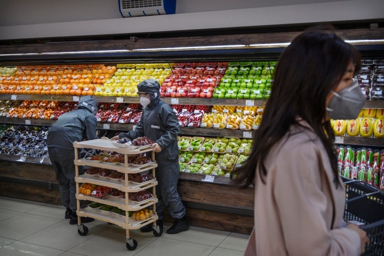 Chinese workers wear protective suits and masks as they stock fruit at a supermarket