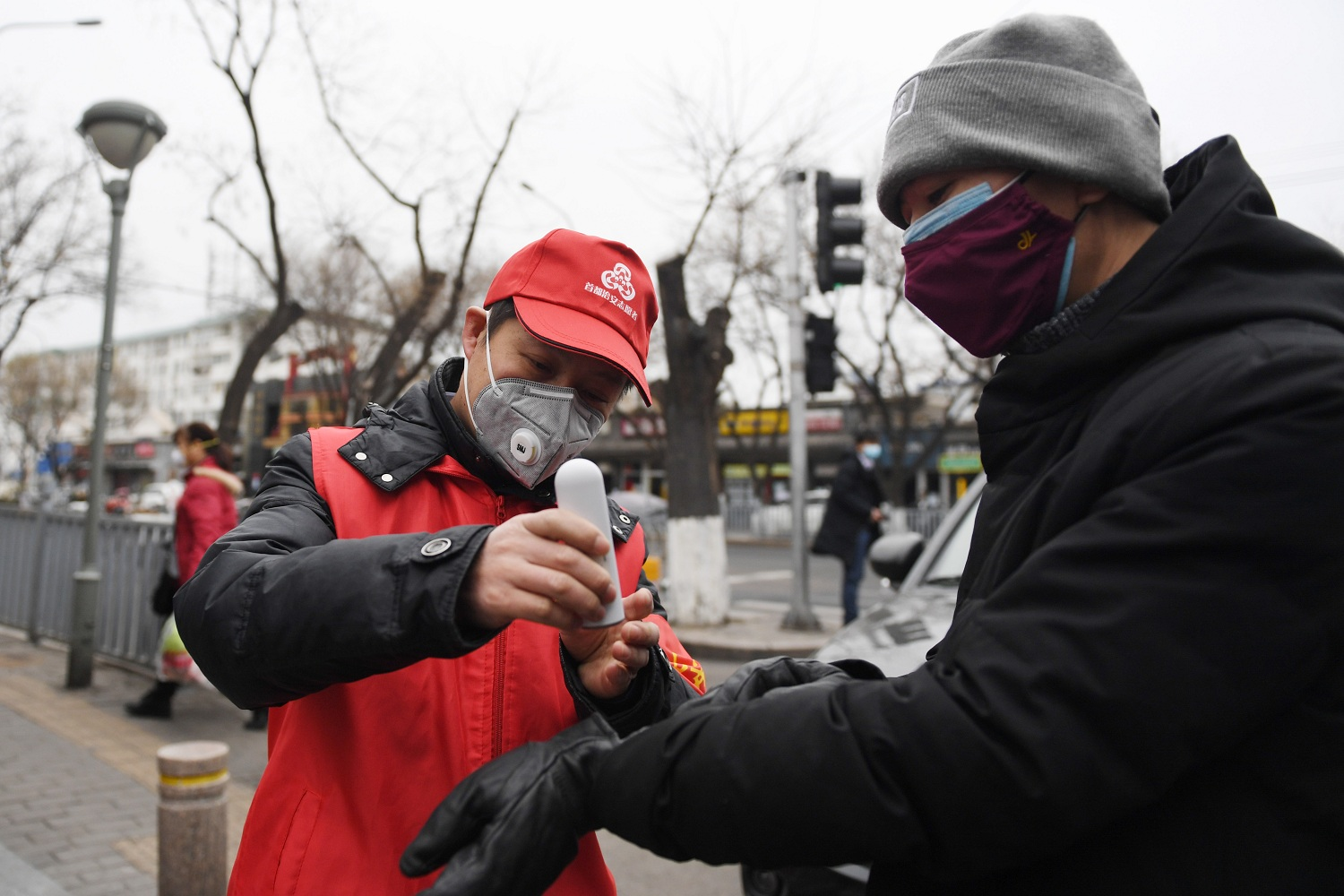 Volunteer Zhang Jianguo L takes the temperature of a resident at the entrance of Cheniandian Lane in Beijing