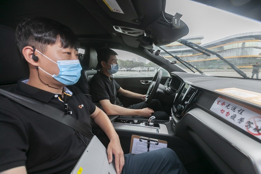 A tester front holds a device to record data in an autonomous vehicle in Shanghai