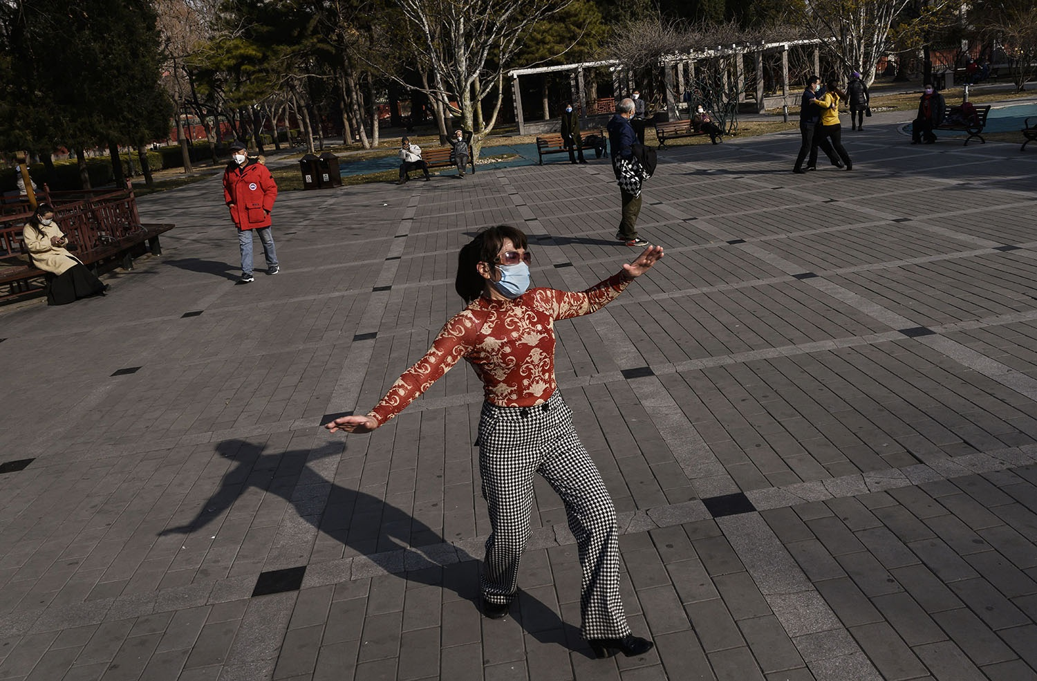 A Chinese woman wears a protective mask as she dances in a sparsely attended park in Beijing