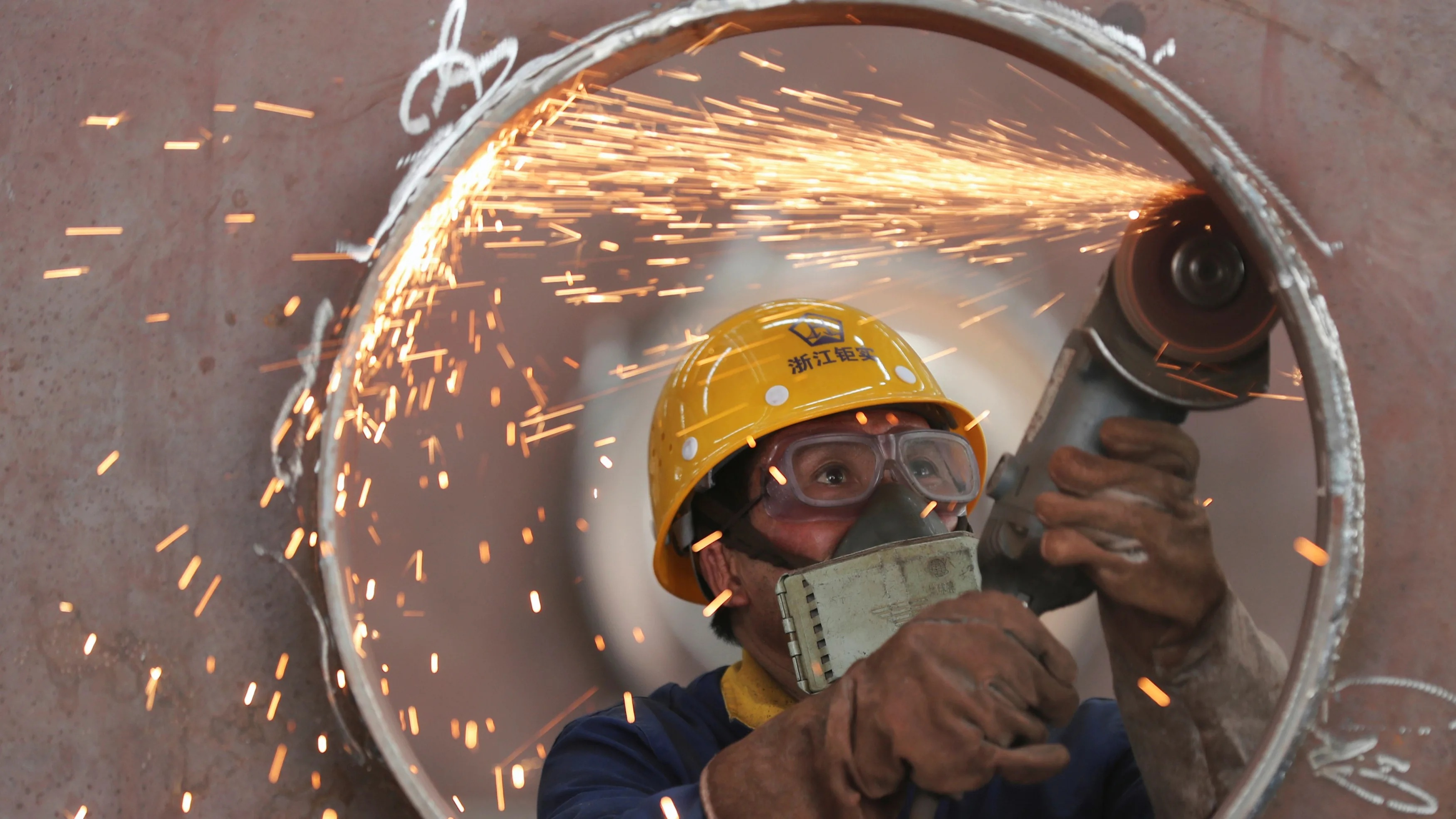 An employee works on a production line manufacturing steel structures at a factory in Huzhou
