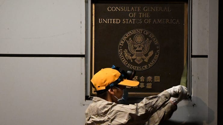 A worker attempts to remove the wall insignia of the U.S. consulate in Chengdu