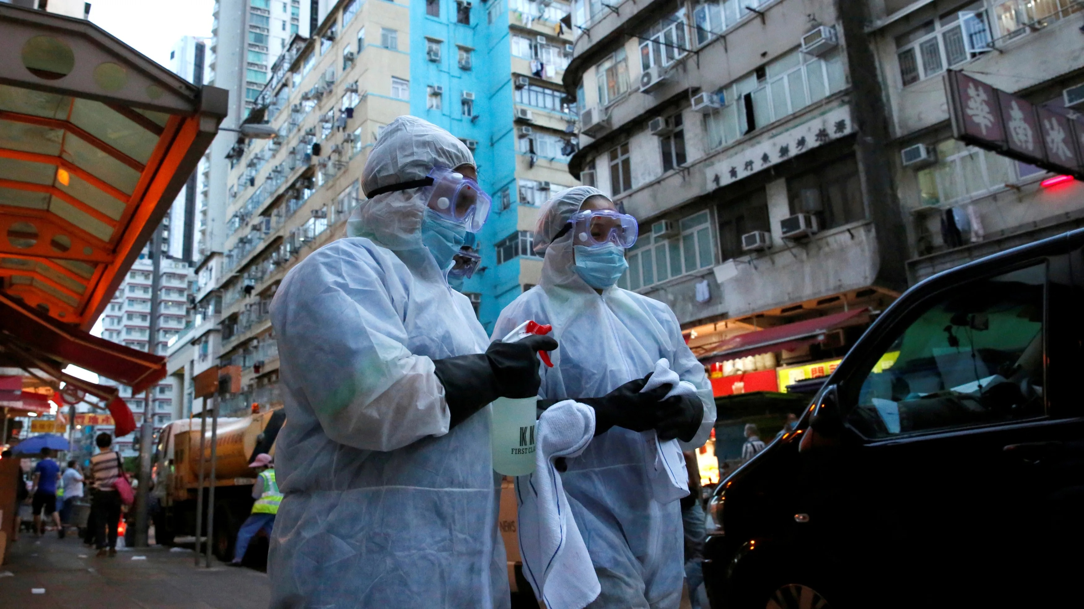 Cleaning workers wearing protective gear walk past a wet market following the coronavirus disease outbreak at Sham Shui Po one of the oldest districts in Hong Kong